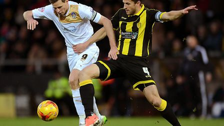 Chris Porter of Colchester United does battle with John Mousinho of Burton Albion. Picture by Richa