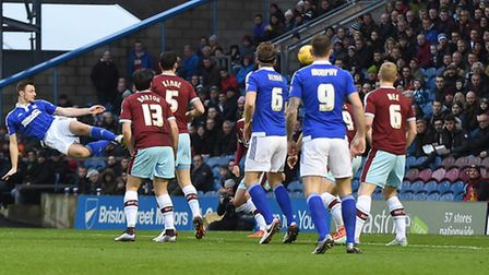 An airborne Tommy Smith diverts the ball towards goal with his head during the first half at Burnley