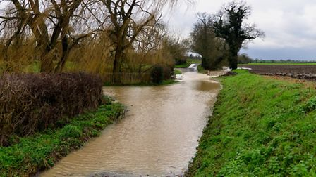 Flood water rushes across Low Road, debenham where a car become stuck.
