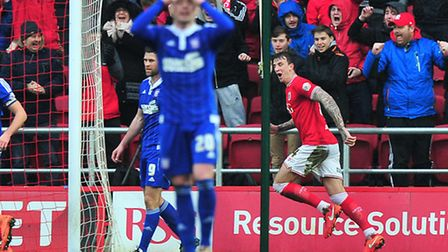Aden Flint of Bristol City celebrates scoring a goal to the dejection of Freddie Sears of Ipswich To