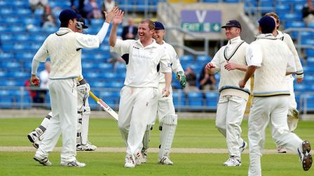 Yorkshire's Anthony McGrath (centre) celebrates with team-mate Michael Vaughan (left) after taking t