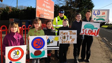 Pupils at All Saints Primary School in Winfarthing hold up their anti-speed signs with PCSO Aslaug F