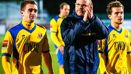 AFC Sudbury Assistant manager Andy Reynolds applauds the supporters as he leaves the pitch with Crai