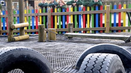Pupils at Benhall Primary School look at the play area which has been left incomplete