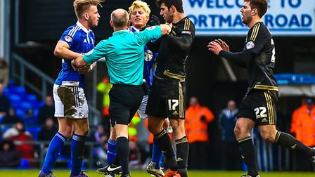 Referee Andy Woolmer gets between Luke Hyam and Nelson Oliveira as tempers flare during the Ipswich