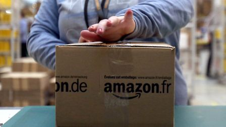 A worker tapes shut a parcel in the Amazon fulfilment centre in Peterborough. Photo: Chris Radburn/