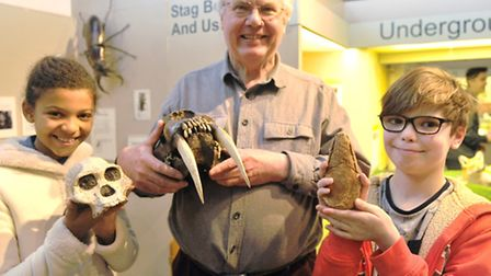 Leyla Huo, 11, and Flynn Worley, 10, hold fossils and skulls with Bob Markham, from Geo Suffolk, at