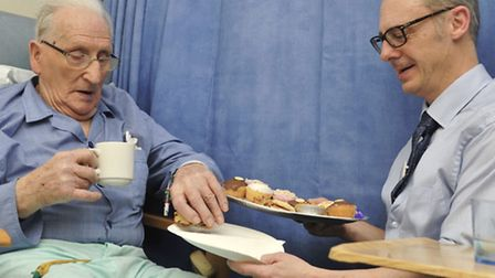 Chief Executive Frank Sims, hands out cakes to Ron Ellis, a patient at Colchester General Hospital,