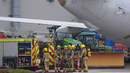 Emergency services at Norwich Airport as an aircraft is removed from the hanger where a fire took ho