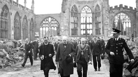 Winston Churchill walks through the ruined nave of Coventry Cathedral after it was wrecked in the Bl
