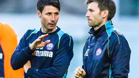 Braintree manager Dan Cowley (left) discusses tactics with his brother and assistant Nicky during th