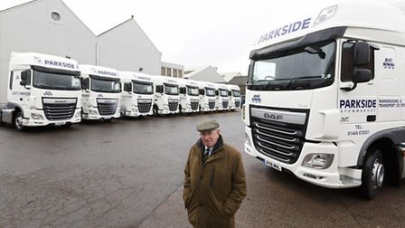 Roy Holloway, chairman of Parkside Warehousing and Transport, with the company's nine new trucks.
