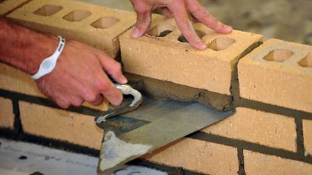 File photo dated 06/10/11 of a trainee bricklayer. Chancellor of the Exchequer George Osborne delive
