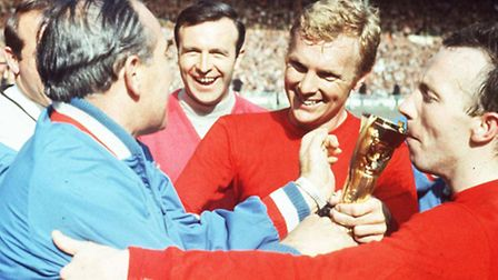 England captain Bobby Moore is congratulated by manager Alf Ramsey as Nobby Stiles kisses the trophy
