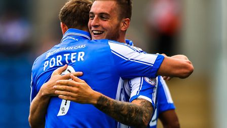 Brennan Dickenson is congratulated by teammate Chris Porter after his goal had put the home side 1-0