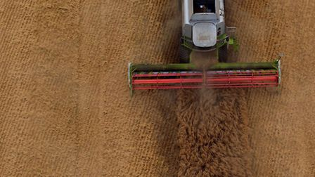 An aerial view of a combine harvester working in a field. Photo: Steve Parsons/PA Wire
