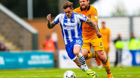 The U's Sammie Szmodics on the ball with Darren Jones of Newport County in pursuit, during the Colch