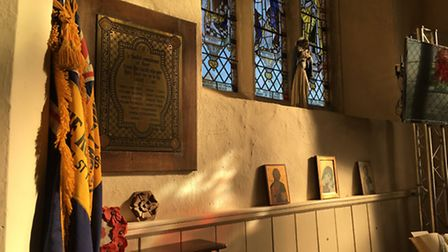 This view of the church shows the plaque on the wall. The book of remembrance is below it