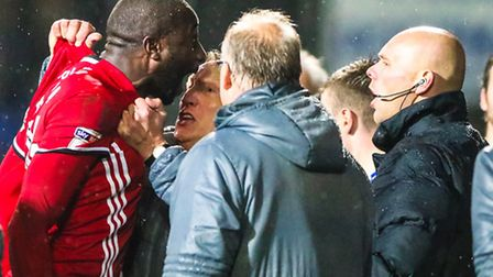 Cardiff City manager Neil Warnock hangs onto Sol Bamba as he argues with fourth official Charles Bre
