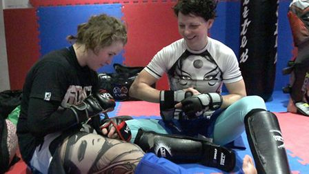 Cory McKenna putting on protective sparring gear with mum Wendy McKenna (right)