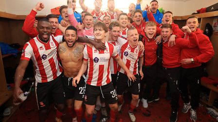 Lincoln City players celebrate their victory in the changing rooms