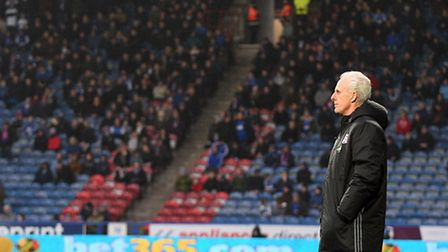 Mick McCarthy at Huddersfield on Saturday with the travelling Ipswich support in the background. Pho