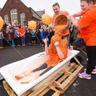 Headteacher of Trimley St Martin Primary School, Samantha Ross, sitting in a bath full of baked bean