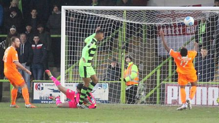 The ball just eludes Michael Cheek (left ) and Reece Hall-Johnson in the Forest Green penalty area o
