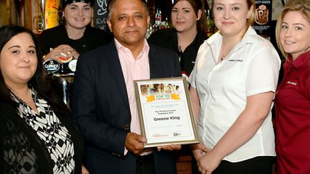Greene King chief executive Rooney Anand with a group of Greene King apprentices at the Spread Eagle