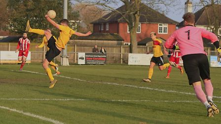 Walsham's Nathan Clarke clears the danger with his keeper left stranded