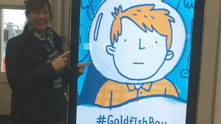 Lisa Thompson at Ipswich station with one of the ads for her book The Goldfish Boy