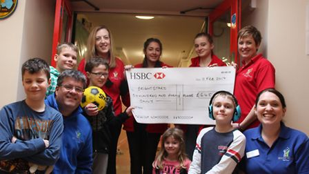 Co-founder Steve Turpie plus volunteers and children from the Brightstars Saturday Club with the che