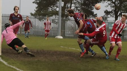 Thetford keeper, Kingsley Barnes clears the ball away from the on-rushing Craig Jennings