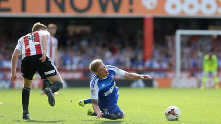 Teddy Bishop is brought down by Lewis MacLeod during a game at Brentford