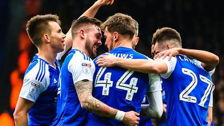 Ipswich goal scorer Emyr Huws congratulated by skipper Luke Chambers and other Town teammates after
