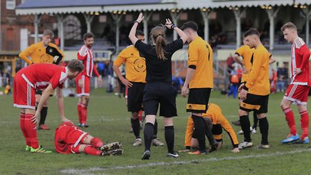 Players look concerned as Referee Abi Marriott calls on both physios