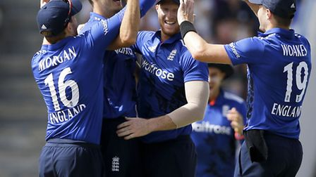 Fun in the sun. England's bowler Steven Finn, second from left, is greeted by teammates after he cau