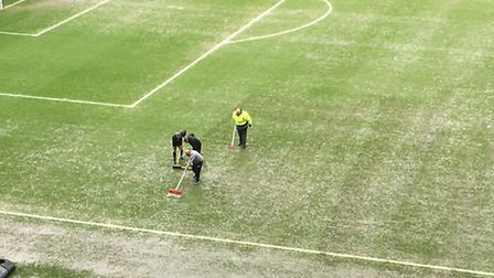 Groundstaff sweeping off some of the surface water at Gresty Road