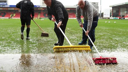 Ground-staff work hard to clear the pitch of water at Gresty Road during the final hour before kick-