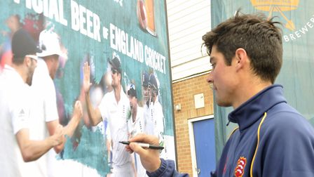 Alastair Cook signs his name on a photo of himself at the Essex County Cricket Club. It is hoped Coo