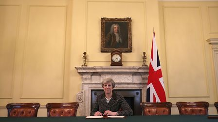 British Prime Minister Theresa May in the cabinet, sitting below a painting of Britain's first Prime