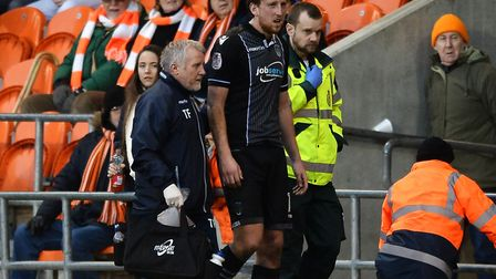 Tom Eastman is helped off the pitch after injuring ankle ligaments at Blackpool on Fbruay 4. But he