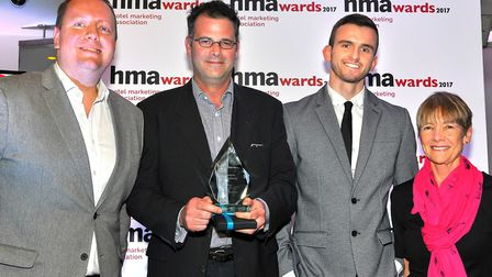 Alex Paul, holding trophy, and Tom Dirscoll, third from left, of Gough Hotels, receive the Best Web