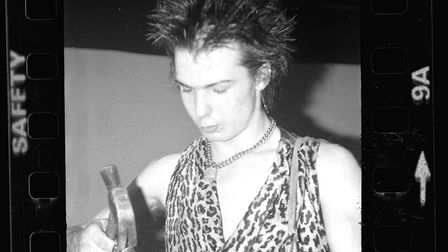 Sid Vicous wielding a hammer backstage at his first gig with The Sex Pistols in 1976. This image is