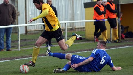 Mildenhall's Chris Bacon in action against Ipswich Wanderers' Kris Rose. Picture Phil Morley