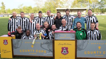 Woodbridge Town celebrate with the Suffolk FA Veterans' Cup after their last-gasp win against Bury T