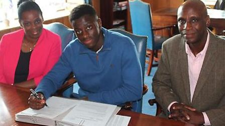 Emmanuel with his parents when signing a two-year deal.