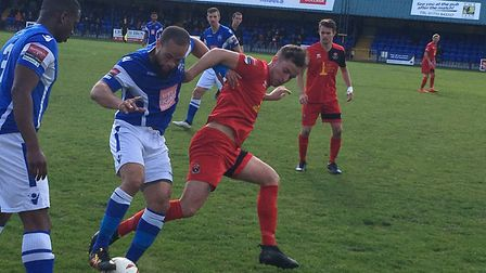 AFC Sudbury midfielder Sam Corcoran (red shirt) challenges for the ball during today's defeat at Ton