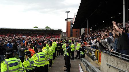 Leyton Orient fans invade the pitch to protest against their board, while Colchester United fans in