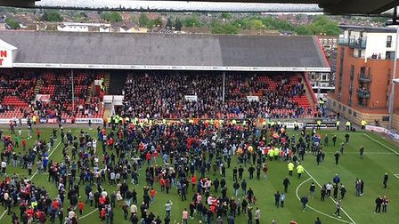Leyton Orient fans on the pitch, Colchester United supporters still in the stand behind them. Today'